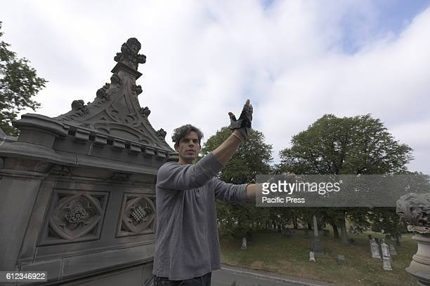 Artist Aaron Asis atop GreenWood Chapel roof describing the origins of his vision for the piece Conceptual artist Aaron Asis began the installation...
