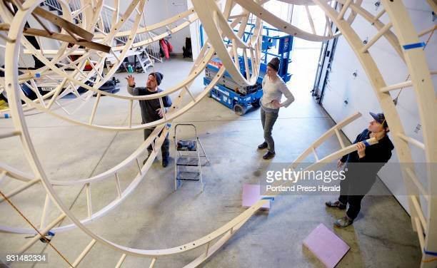 Artist Aaron T Stephan talks with his studio assistants Elizabeth Kleene center and Tessa O'Brien as they disassemble Aaron's wooden sculpture Paths...