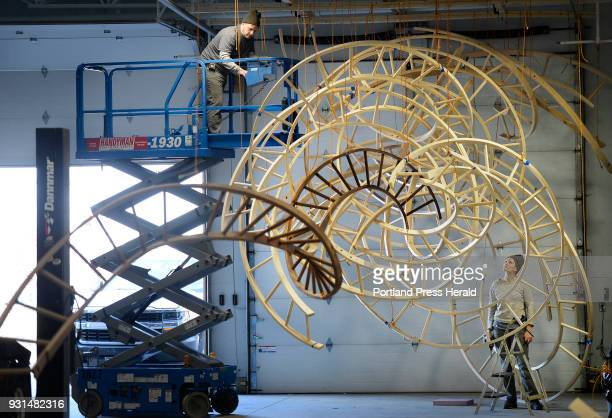 Artist Aaron T Stephan uses a lift as he disassembles his wooden sculpture Paths Woven along with the help of studio assistant Elizabeth Kleene at...