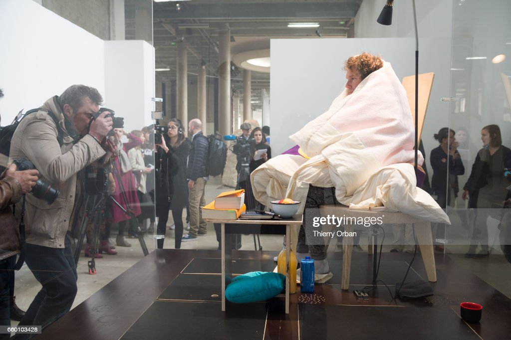 Artist Abraham Pointcheval sits on chicken eggs during his performance of 'Oeuf', during which he will experience gestation by replacing a hen until the eggs hatch at Palais De Tokyo on March 29, 2017 in Paris, France.