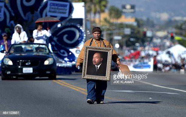 Artist Al Hornsby walks with his painting of Martin Luther King Jr as he participates in the Martin Luther King Jr parade in Los Angeles California...