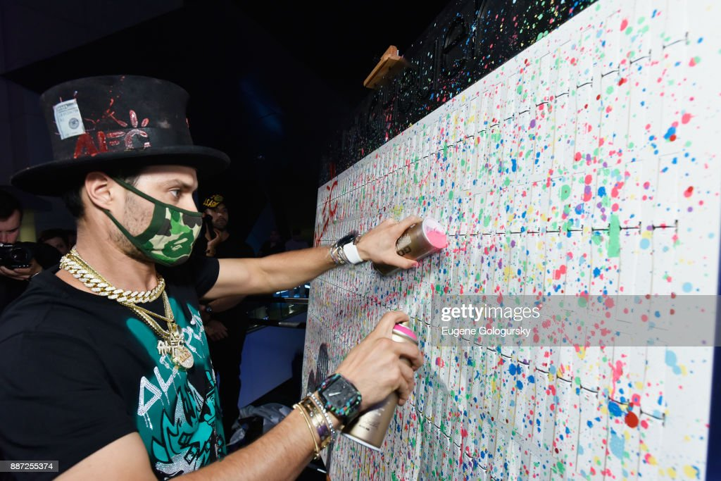 Artist Alec Monopoly customizes his special design onstage at Art Basel Miami Beach pre-show with TAG Heuer Art Provocateur Alec Monopoly at Miami Design District on December 6, 2017 in Miami, Florida.