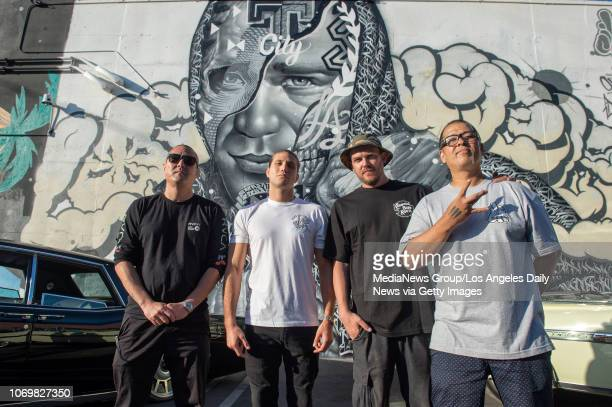 Artist Alex Kizu topranked UFC featherweight Brian Ortega artist Tristan Eaton and artist Richard Wyrgatsch II in front of a mural of Ortega that the...
