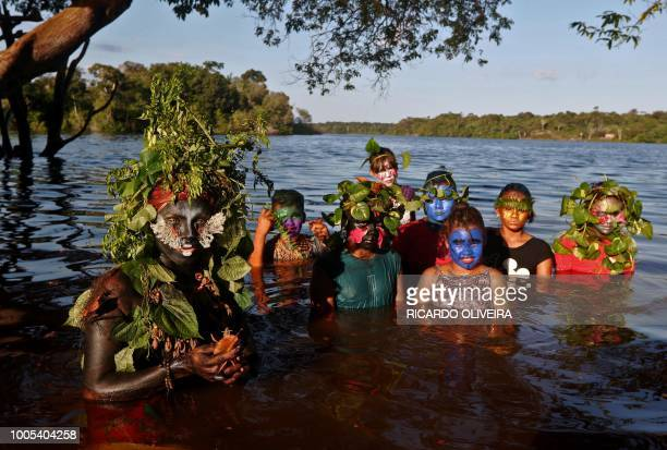 Artist and activist Emerson Munduruku poses with children to whom he teaches environmental conservation through his drag queen alter ego character...