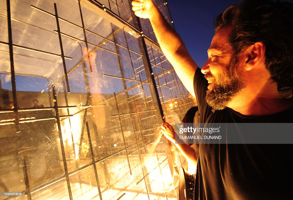 Artist and developer David Belt takes part in his latest project 'Glassphemy!' on May 20, 2010, in Brooklyn, New York. �Glassphemy!,� is billed as a psychological recycling experiment, in which people stand on a high and a low platform set on each end of a 20-foot-by-30-foot clear box, with high walls made of steel and bulletproof glass. Those on the higher platform take empty glass bottles and throw them at their compatriots across the way protected by a bulletproof glass. The bottles smash at the tempo of artfully designed lights flash. The idea is to make recycling a more direct, visceral experience and to purge some of New York aggression simultaneously. AFP PHOTO/Emmanuel Dunand