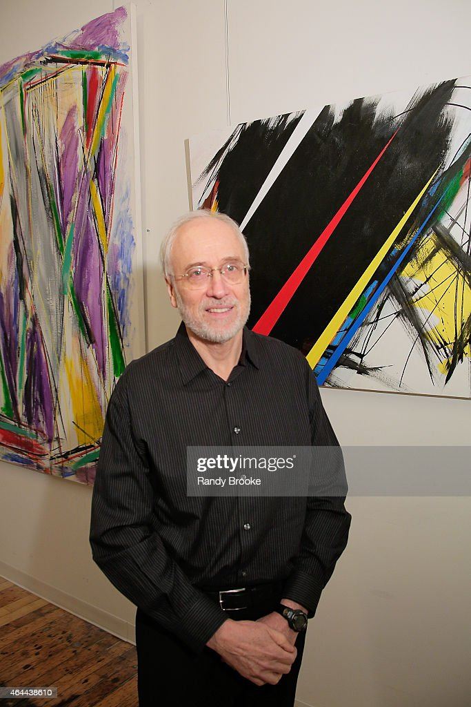Artist and Film Producer Joe Fisher poses in front of one of his paintings during the FilmRise Celebrates new office in Industry City, Brooklyn at FilmRise on February 25, 2015 in Brooklyn, New York.