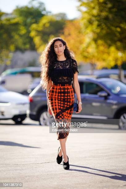 Artist and singer Ciinderella B wears a black lace mesh ruffle top, an orange checked skirt outside Rochas, during Paris Fashion Week Womenswear...