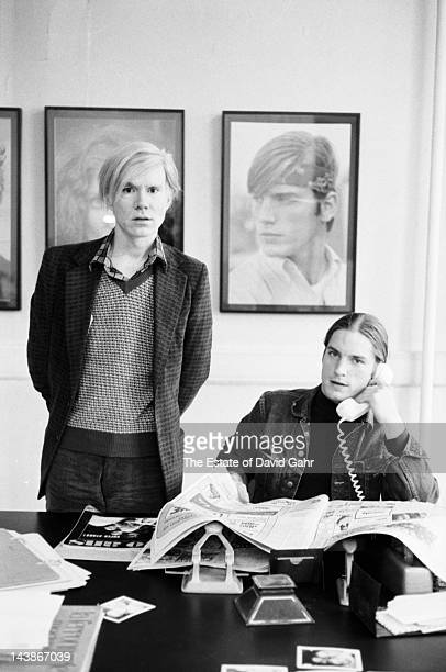 Artist Andy Warhol and actor and Warhol 'superstar' Joe Dallesandro pose for a portrait at the 'new' Factory Warhol's studio and business offices on...