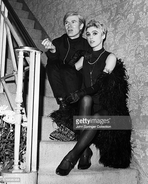 Artist Andy Warhol and Edie Sedgwick, who wears a black feather boa, sit on a staircase chatting. Undated photo.