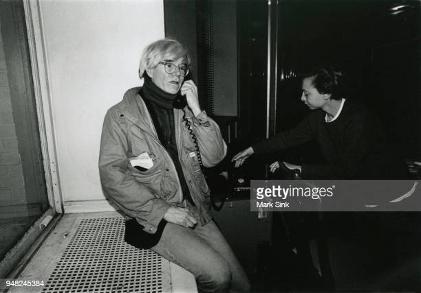 Artist Andy Warhol takes a late night phone call on the windowsill of the Factory at 860 Broadway on March 4 New York City New York