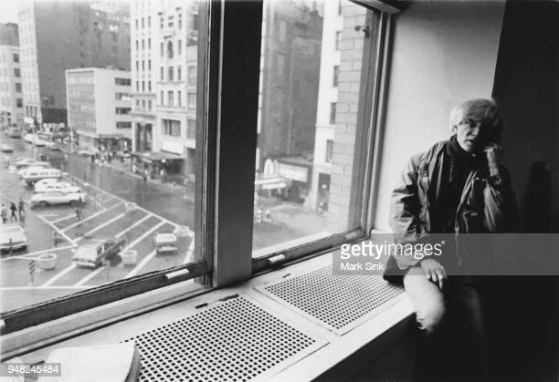 Artist Andy Warhol takes a phone call on the windowsill of the Factory at 860 Broadway on March 4 New York City New York