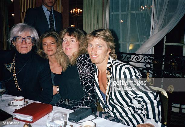 Artist Andy Warhol with fan Catherine Guinness and photographer Christopher Makos Cafe Royal London 8th July 1986 Pictured at a dinner party after...