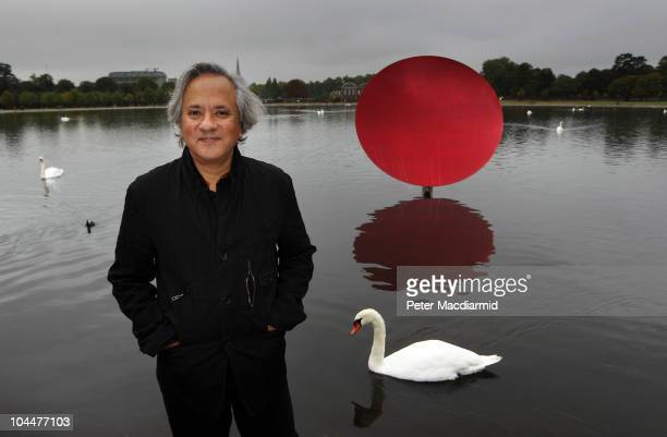 Artist Anish Kapoor stands in front of his sculpture Sky Mirror Red 2007 in Kensington Gardens on September 27 2010 in London England Four works are...
