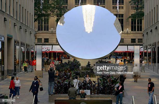 Artist Anish Kapoor's Sky Mirror reflects area buildings in Rockefeller Plaza as people go about their business The public art piece will be on...
