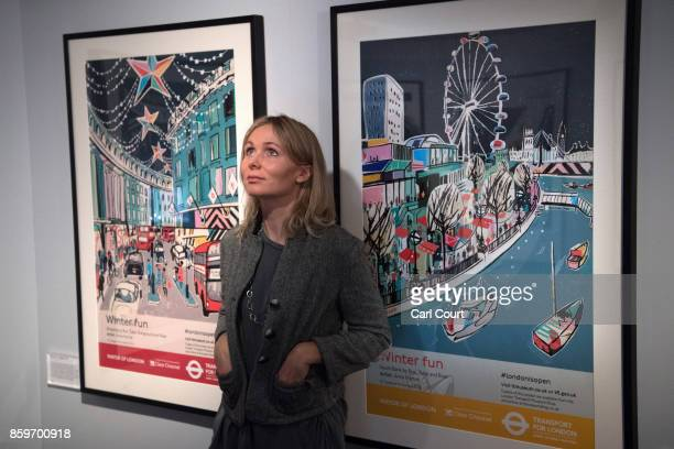 Artist Anna Hymas poses next to her artworks entitled 'Winter funshopping' and 'Winter fun South Bank by Bus Tube and River' during a press preview...