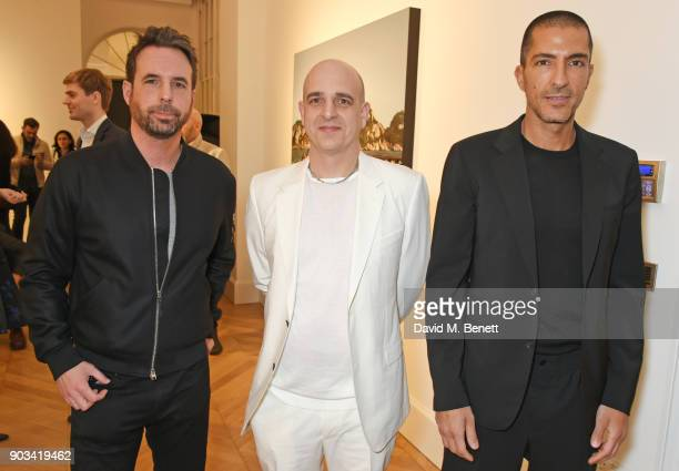 Artist Antony Micallef Steve Lazarides and Wissam Al Mana attend the private view of 'JR Giants Body of Work' at Lazinc on January 10 2018 in London...