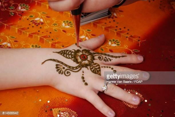Artist applying henna on women's hand