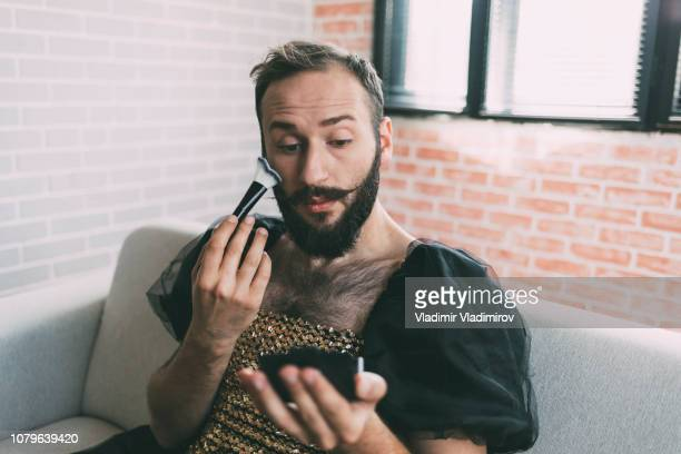 artist applying make-up and wears a dress - transvestite stock photos and pictures