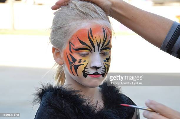 Artist Applying Tiger Paint On Girl During Halloween
