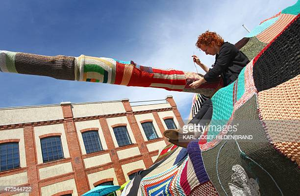 Artist Barbara Niklas puts finishing touches on her work consisting of a Leopard 1 tank wrapped into a knitted shell on May 8 2015 in Augsburg...