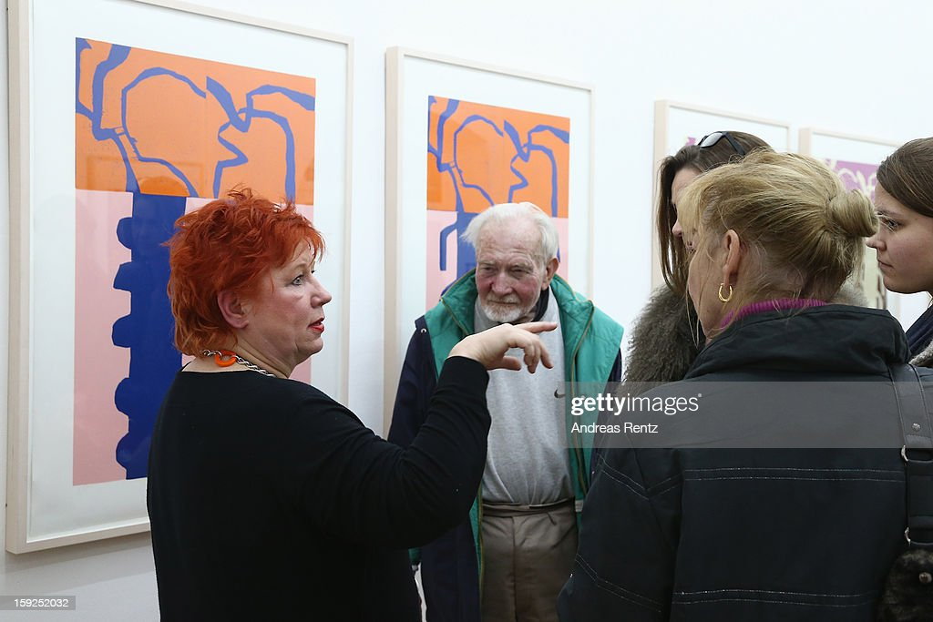 Artist Barbara Salesch (L) talks to guests next to her art work (title: 'Farbserie 1 - 7teilig') at ROOT gallery on January 10, 2013 in Berlin, Germany. The exhibition will open January 10 and run through February 3.