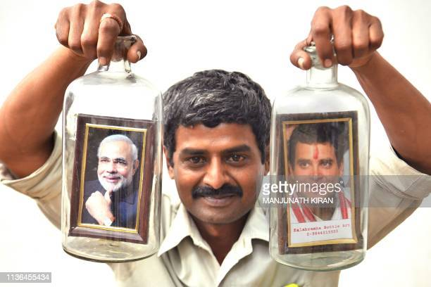 Artist Basavaraj poses with is bottle art creation of placing framed portraits of Indian Prime Minister Narendra Modi and President of Indian...