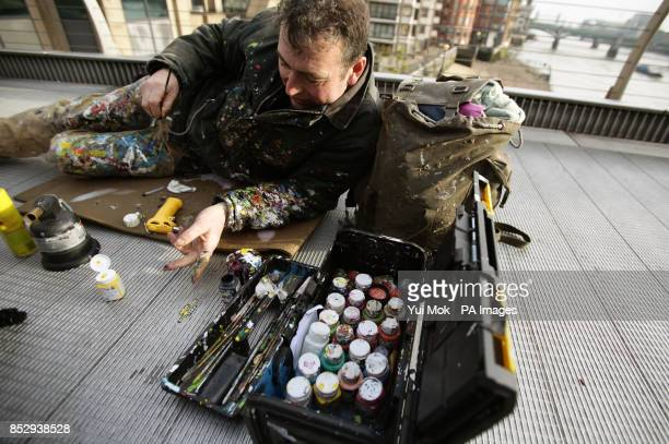 Artist Ben Wilson who paints art on discarded gum and is also known as 'Chewing Gum Man' at work on the Millennium Bridge in London