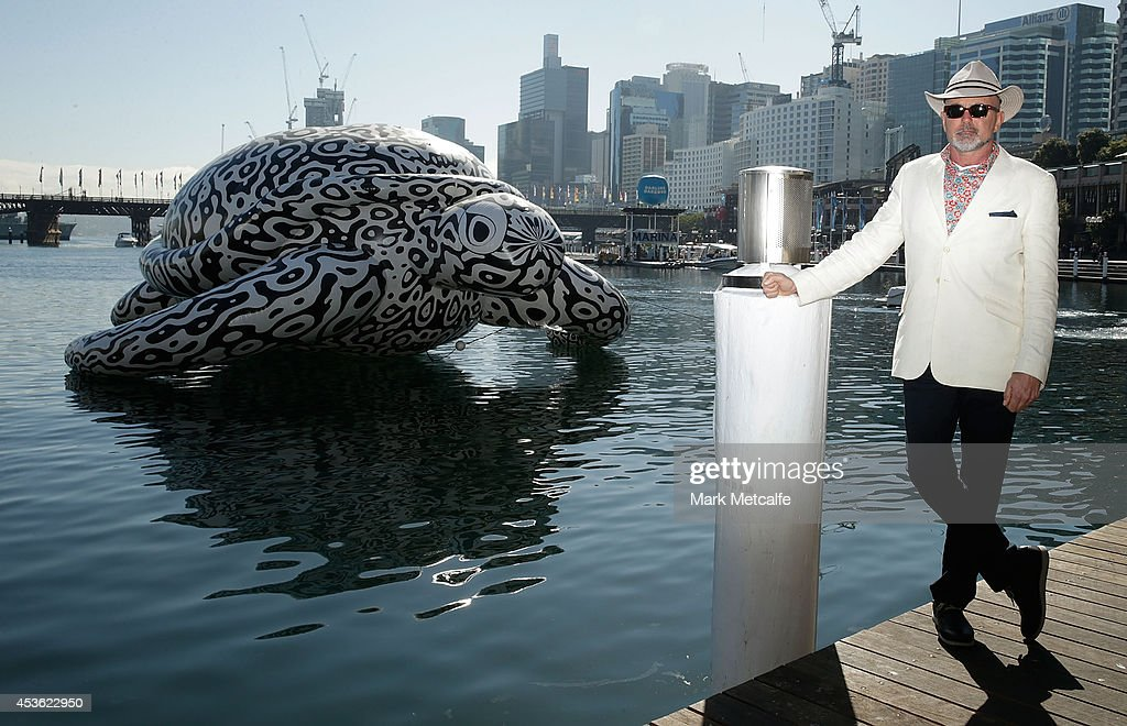 Artist BJ Price poses in front of a 5 metre tall, 15 metre long Sea Turtle that is emblazoned with his artwork 'Alpha' at Darling Harbour on August 15, 2014 in Sydney, Australia.