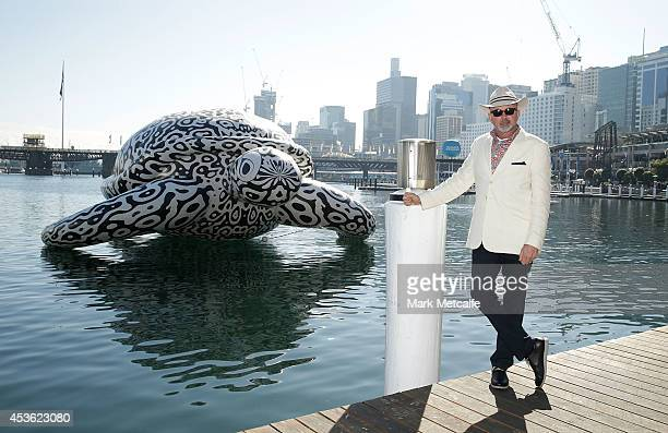 Artist BJ Price poses in front of a 5 metre tall 15 metre long Sea Turtle that is emblazoned with his artwork 'Alpha' at Darling Harbour on August 15...
