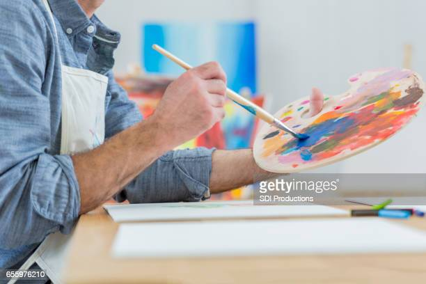 artist blends paint on an artist's palette - painted image stock pictures, royalty-free photos & images