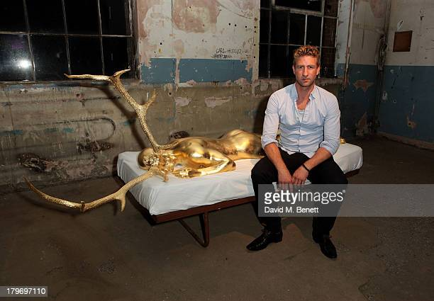 Artist Carl Hopgood poses with his artwork at a private view of the Platform Six exhibition with adidas Originals Stan Smith auction in support of...