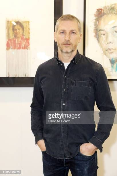 Artist Charming Baker poses with his portrait from the Unmissable25 exhibition during the private view of The Other Art Fair at The Old Truman...