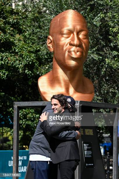 """Artist Chris Carnabuci and Terrence Floyd embrace in front of the """"Floyd"""" sculpture during the Confront Art's First Exhibition launch SEEINJUSTICEin..."""