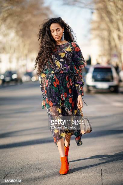 Artist Ciinderella B wears a multicolor pleated lace floral print dress a Chloe bag earrings orange shoes outside Dior during Paris Fashion Week...