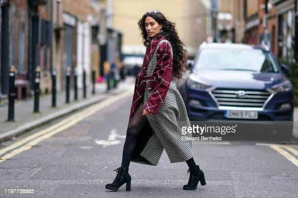 Artist Ciinderella B wears sunglasses, earrings, a red black and white houndstooth pattern print long trench coat, black shoes, during London Fashion...