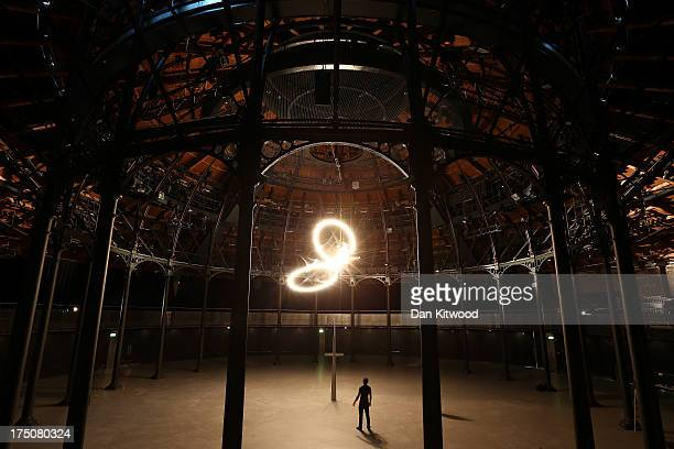 Artist Conrad Shawcross stands under an installation called 'Timepiece' at The Roundhouse on July 31 2013 in London England The largescale light...