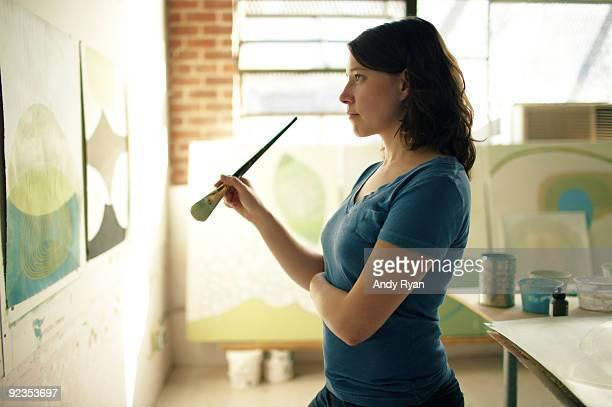 Artist contemplating painting in studio