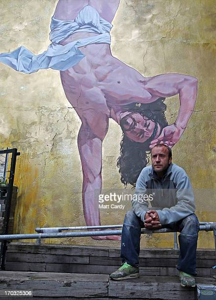 Artist Cosmo Sarson sits besides a giant mural of Jesus breakdancing that he has painted on the 85 metre wall beside The Canteen in Stokes Croft and...