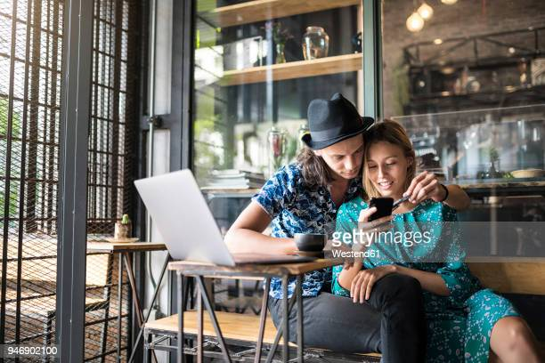 Artist couple sitting in cafe and checking the young womans smartphone