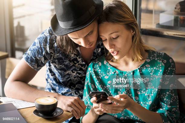 Artist couple sitting in cafe and checking the young womans