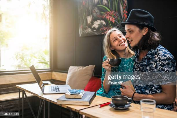 Artist couple sitting in cafe and having fun together