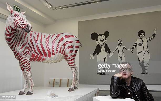 Artist Damien Hirst poses for photographers in front of a sculpture titled 'Stripped ' by Michael Joo and a work by the artist Banksy titled 'Can't...