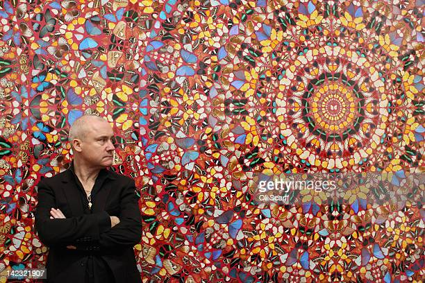 Artist Damien Hirst poses in front of his artwork entitled 'I am Become Death Shatterer of Worlds' in the Tate Modern art gallery on April 2 2012 in...