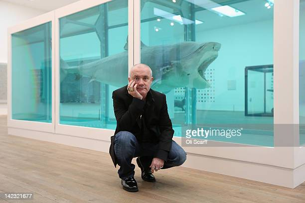 Artist Damien Hirst poses in front of his artwork entitled 'The Physical Impossibility of Death in the Mind of Someone Living' in the Tate Modern art...
