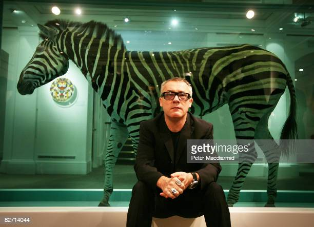 Artist Damien Hirst sits in front of his piece 'The Incredible Journey' featuring a zebra in formaldehyde at Sotheby's auction 'Beautiful Inside My...