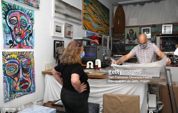 Artist Dani Asher talks with gallery owner/artist John Lindsey as he wraps a framed piece of art for her at the Great Highway Gallery on Tuesday,...