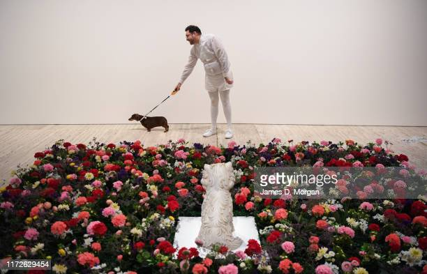 Artist David Capra and his sausage dog Teena looking at the exhibit Puppy by Jeff Koons during a media preview for Making Art Public 50 years of...