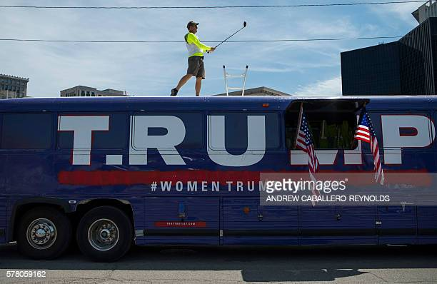 Artist David Gleeson swings a golf club on the top of a former Trump bus used by the campaign in Iowa and now used as protest art after being bought...