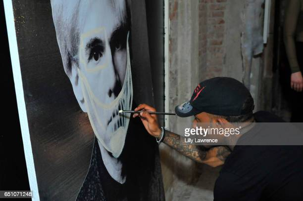 Artist Dee Cosey paints on site at Karen Bystedt's 'Kings And Queens' exhibition on March 9 2017 in Los Angeles California