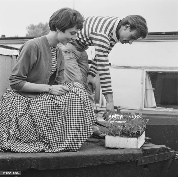 Artist Derek Jukes watering plants on his houseboat 'Coot' moored on the Thames by Cheyne Walk Chelsea London September 1959